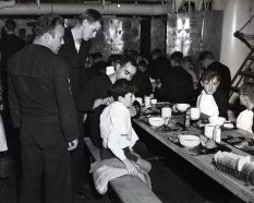 """Photo ID: 80-G-207320. Original caption: """"War orphans of Malta were Christmas dinner guests aboard the USS Brooklyn (CL-40) in Malta Harbor, each with a sailor escort. Later there were gifts and movies in hangar. Sailors left to right: SM1c JB Bulinkski, Y2c WJ Reysters, and PhMic RV Ingoglio tucking in napkin."""" Date: December 25th, 1943"""