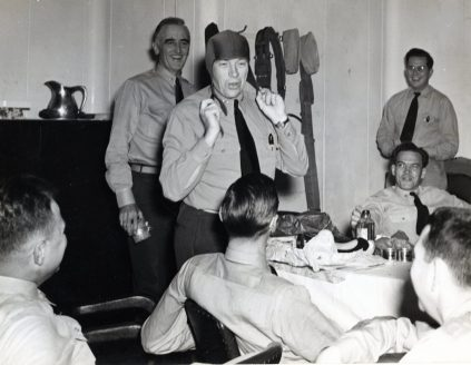 """Photo ID: 80-G-209232. Original caption: """"Celebrating Christmas Eve on board the USS Core (CVE-13) while at sea. Capt. James R. Dudley (USN) tries one of his birthday presents. Comdr. William K. Rhodes (USN, background) issues presents."""" Date: December 24th, 1943"""