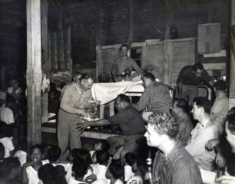 """Photo ID: 80-G-362728. Original caption: """"Natives of Majuro Village Atoll, Marshall Islands, celebrate Christmas. Accepting native-made gifts on behalf of the men under his command, Captain Harold B. Grow (USNR), smiling expresses his appreciation."""" Photographer: PhoM1/c BR Barrett. Date: December 25th, 1944"""