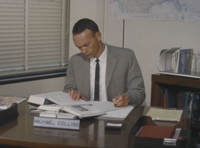 """Astronaut Michael Collins sit behind a desk, reading from a book. Name plate reads """"Michael Collins."""""""