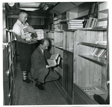 Before leaving Dr. Spring, the Librarian (kneeling), aided by Georg Schoenberger, puts the books back in their places. (306-CS-1B-17) https://catalog.archives.gov/id/23932341