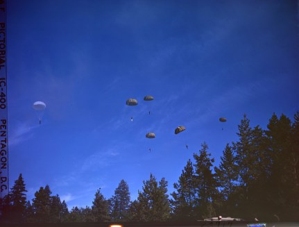 342-C-K3717 148728122 Original Caption: Operation Firefly - Paratrooper of the 555th Parachute Infantry drift toward the tree tops not far from a forest fire. Umatilla National Forest, Oregon.