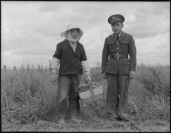 """Original Caption: """"Florin, Sacramento County, California. A soldier and his mother in a strawberry field. The soldier, age 23, volunteered July 10, 1941, and is stationed at Camp Leonard Wood, Missouri. He was furloughed to help his mother and family prepare for their evacuation. He is the youngest of six years children, two of them volunteers in United States Army. The mother, age 53, came from Japan 37 years ago. Her husband died 21 years ago, leaving her to raise six children. She worked in a strawbery basket factory until last year when her children leased three acres of strawberries """"so she wouldn't have to work for somebody else"""". The family is Buddhist. This is her youngest son. Her second son is in the army stationed at Fort Bliss. 453 families are to be evacuated from this area."""" Photographer: Dorothea Lange. Date: May 11, 1942. Local ID: 210-G-A584 (NAID 536474)"""
