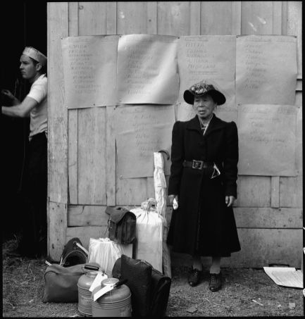 """Original Caption: """"Centerville, California. This evacuee stands by her baggage as she waits for evacuation bus. Evacuees of Japanese ancestry will be housed in War Relocation Authority centers for the duration."""" Photographer: Dorothea Lange. Date: May 9, 1942. Local ID: 210-G-C241 (NAID 537588)"""