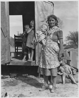 """Original Caption: """"On Arizona Highway 87, south of Chandler. Maricopa County, Arizona. Children in a democracy. A migratory family living in a trailer in an open field. No sanitation, no water. They came from Amarillo, Texas. Pulled bolls near Amarillo, picked cotton near Roswell, New Mexico, and in Arizona. Plan to return to Amarillo at close of cotton picking season for work on WPA."""" Photographer: Dorothea Lange. Date: November 1940. Local ID: 83-G-44358 (NAID 522527)"""