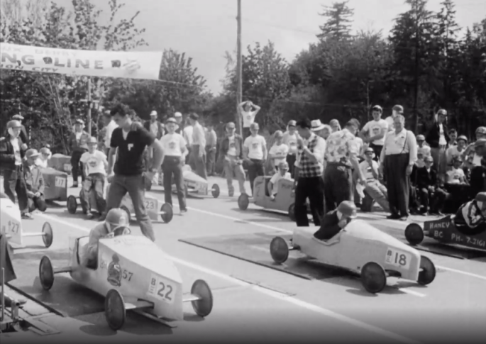 A crowd is gathered as children prepare to start a soap box derby race.