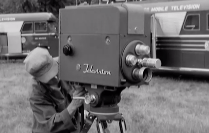 """Image of man in army fatigues setting up a television camera. There are two buses behind him that are labeled """"MOBILE TELEVISION"""""""