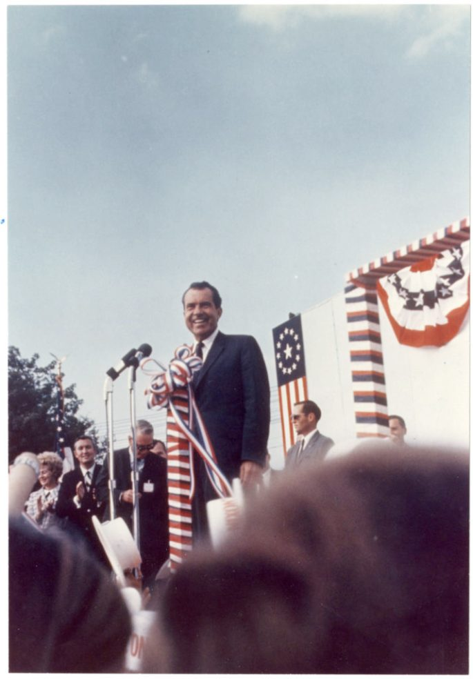 Richard Nixon stands in front of a microphone in front of a backdrop of patriotic bunting and a version of the original United States flag. He is outside and there are people to the side of the stage.