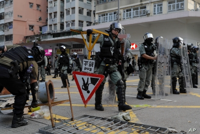 Riot police remove barricades erected by demonstrators during a protest in Hong Kong, Oct. 12, 2019.