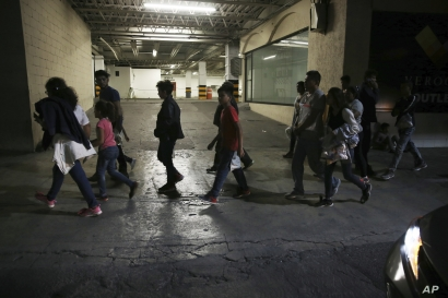 Migrants who have been bused by Mexican authorities from Nuevo Laredo to Monterrey, walk on a street in Monterrey, Mexico, July 18, 2019.