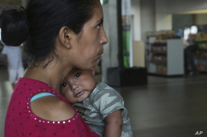A woman and her 7-month-old baby stand on a sidewalk after being bused by Mexican authorities from Nuevo Laredo to Monterrey, Mexico.