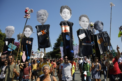 Anti-G-7 activists carry pictures of the G-7 leaders during a protest in Hendaye, France, Aug. 24, 2019.
