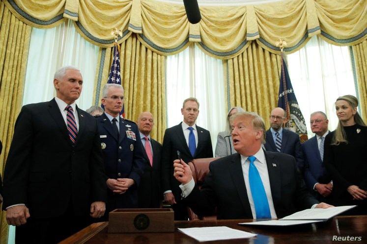 U.S. President Donald Trump looks to Vice President Mike Pence during a signing ceremony to establish a Space Force as part of the U.S. Armed Forces, in the Oval Office at the White House in Washington, Feb. 19, 2019.