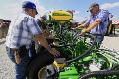 Visitors to the Husker Harvest Days farm show in Grand Island, Neb., look over John Deere equipment, Tuesday, Sept. 10, 2019. (AP Photo/Nati Harnik)
