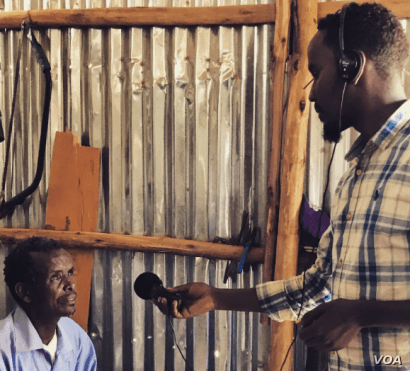 Mahad interviews a man at the Bokolmanyo refugee camp, in Bokolmanyo, Ethiopia. (M. Birungi/VOA)