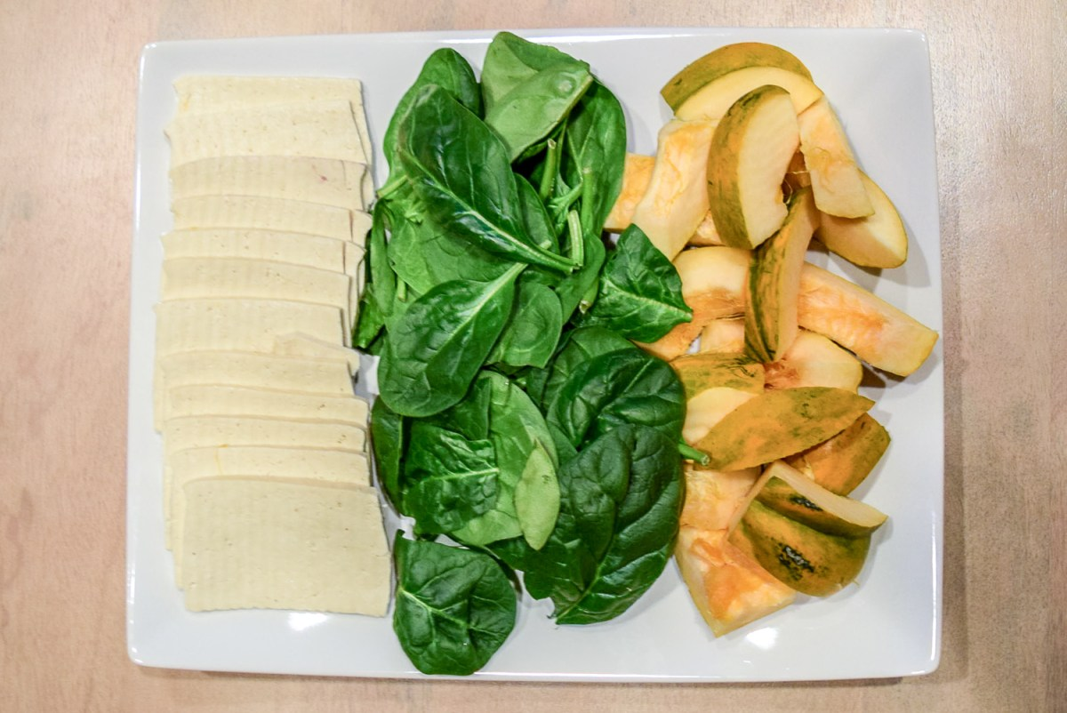 Tofu, spinach, and acorn squash on plate for Instant Pot Hot Pot
