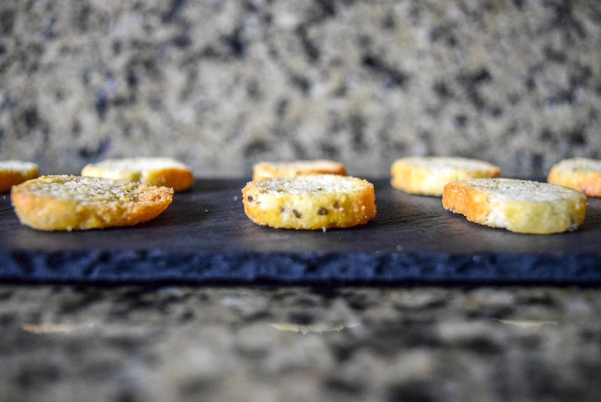 Asturi Rosemary and Olive Oil Bruchettini bread slices laid out on slate cheeseboard from side