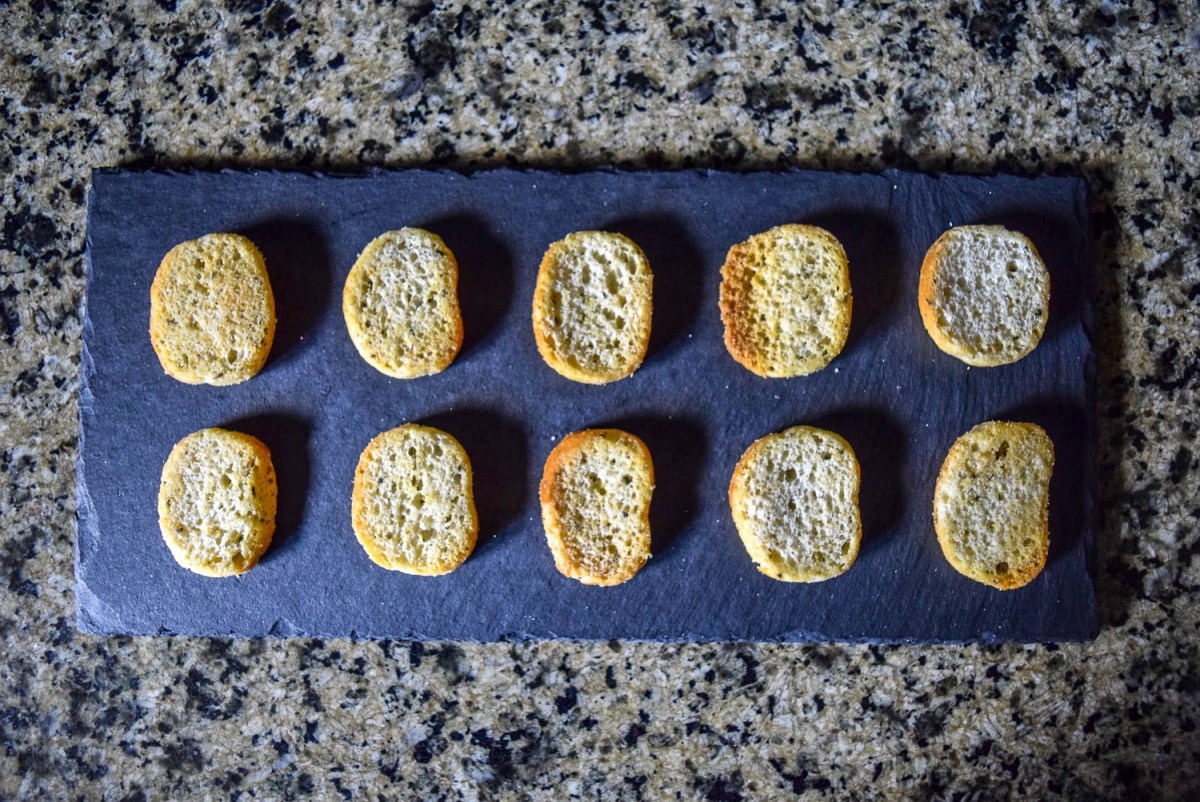Asturi Rosemary and Olive Oil Bruchettini bread slices laid out on slate cheeseboard from top