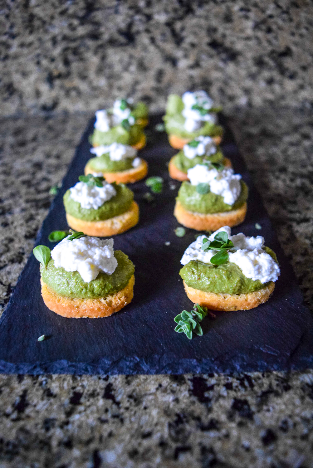 Marjoram Pea Pesto Crostini with Fresh Ricotta on slate cheeseboard from front