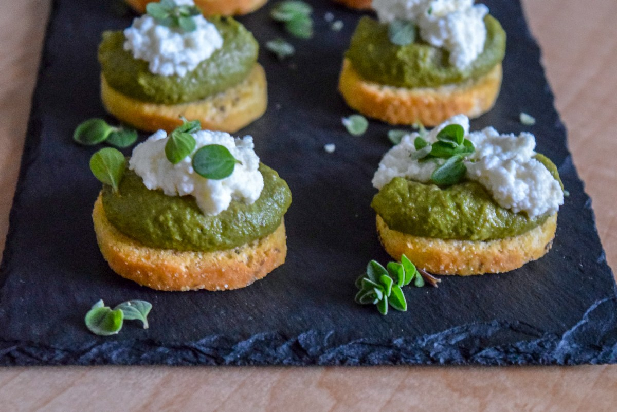 Marjoram Pea Pesto Crostini with Fresh Ricotta on slate cheeseboard from front angle