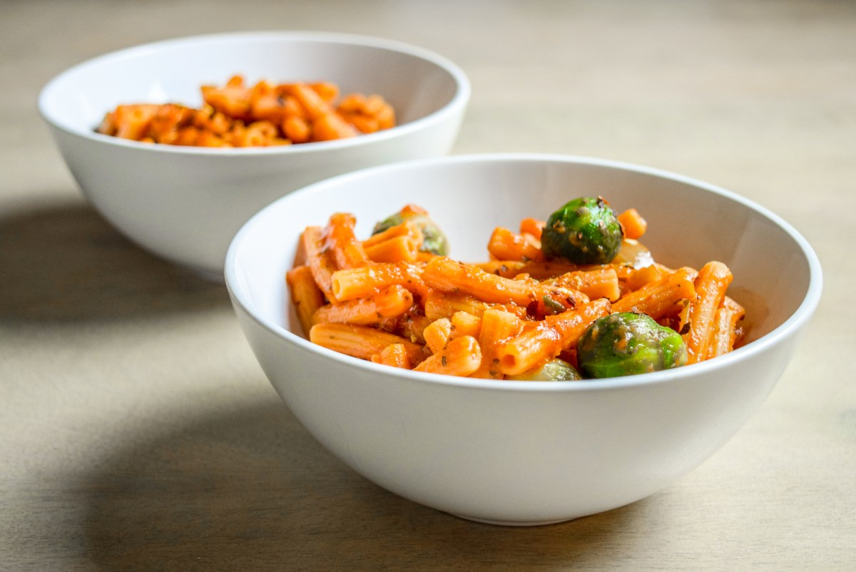Finished Protein-Packed Red Lentil Pasta with Marinara, Brussel Sprouts, and Caramelized Onions in two bowls