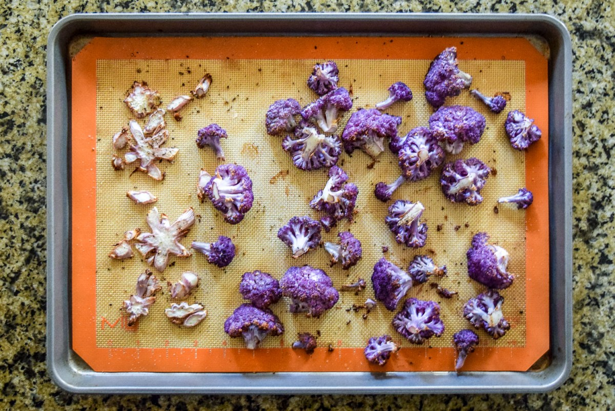 Roasted purple cauliflower florets and stem pieces on silicone baking sheet on calphalon baking sheet from top