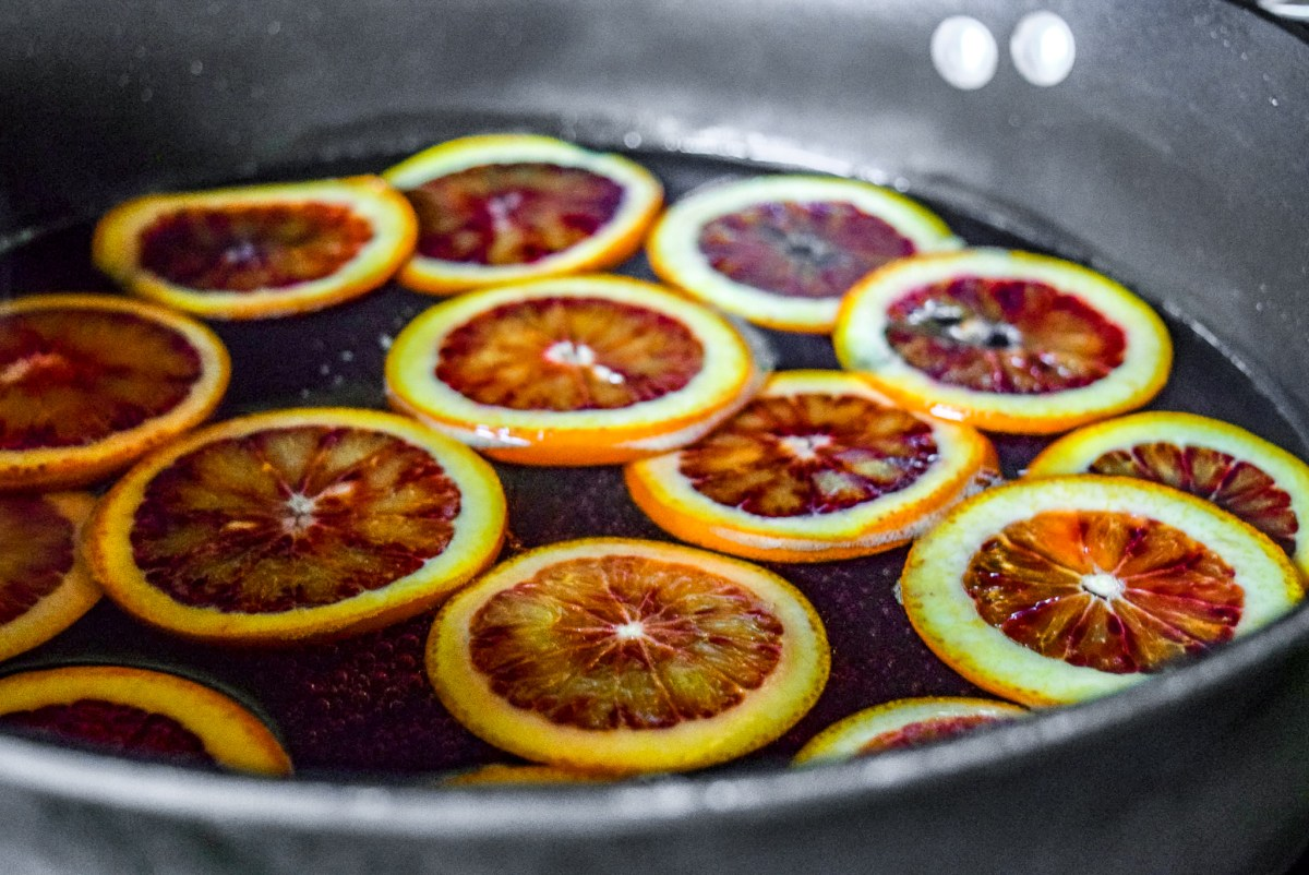 Blood orange slices in sugar water for candying up close