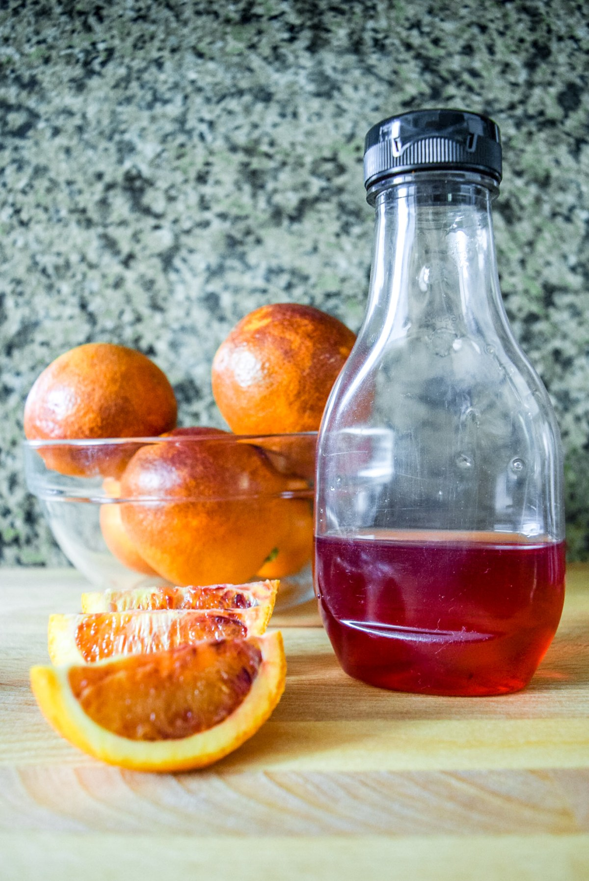 Finished blood orange syrup with sliced blood oranges from top