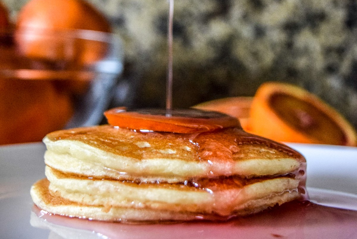 Action shot of pouring homemade blood orange syrup on Trader Joe's frozen pancakes from side up close
