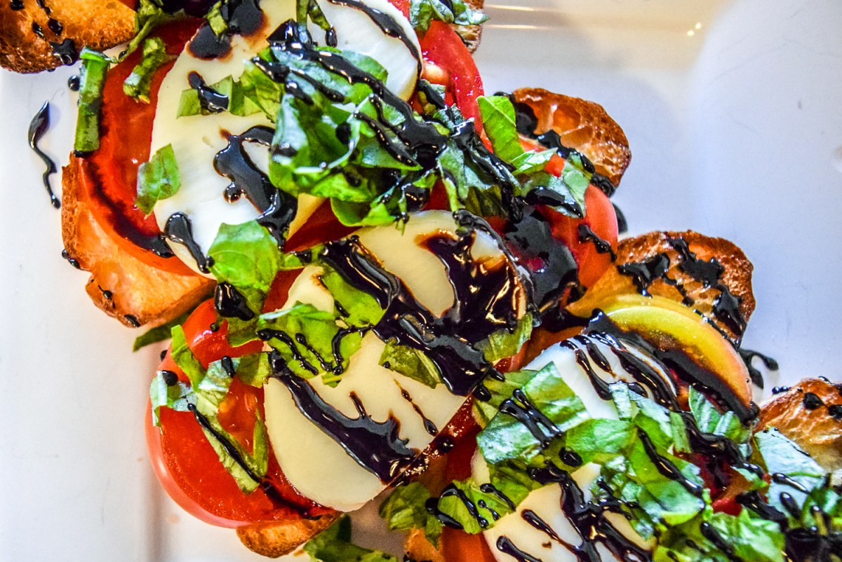Finished caprese bruschetta with heirloom tomato, fresh basil, homemade mozzerella, and balsamic reduction up close