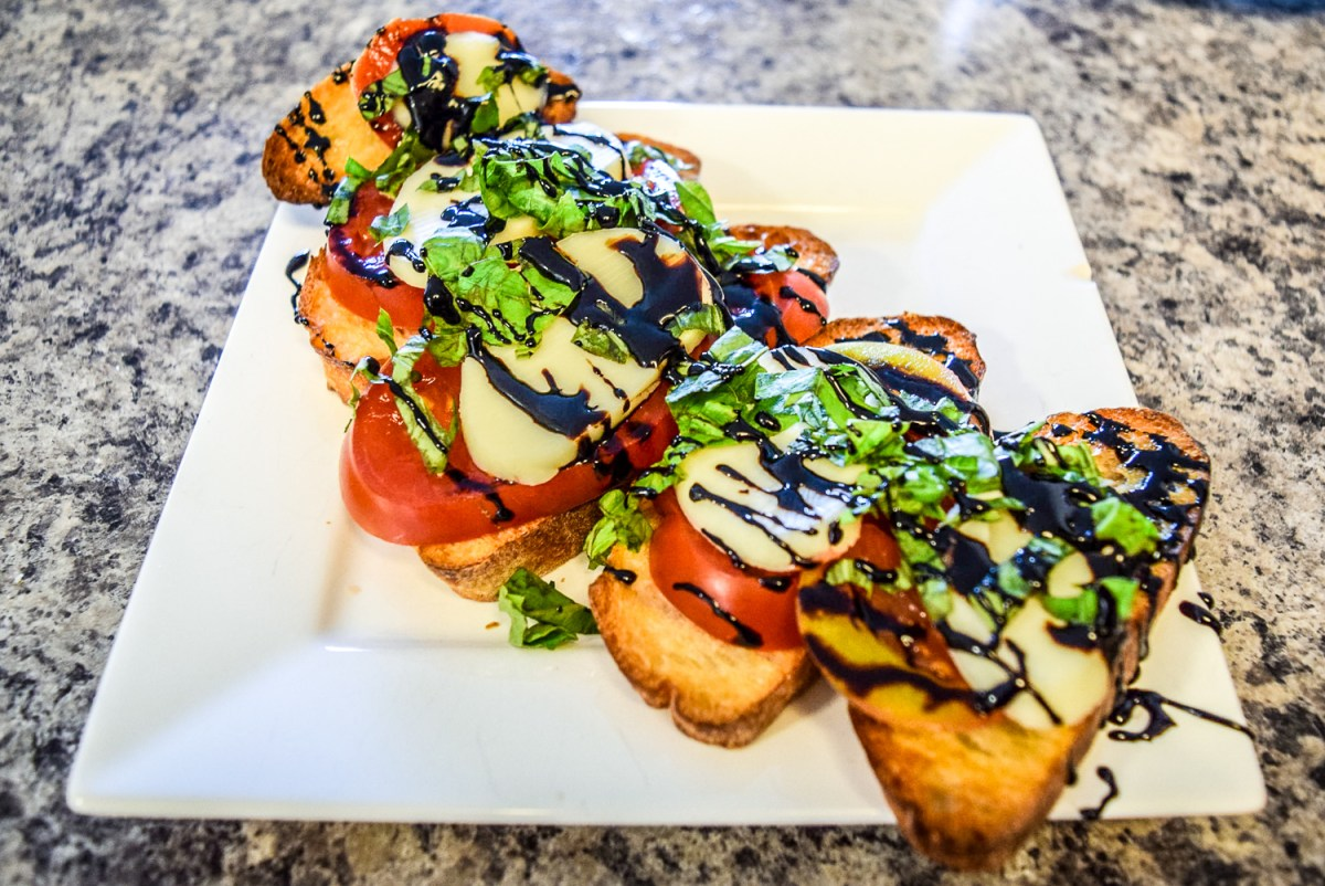 Finished caprese bruschetta with heirloom tomato, fresh basil, homemade mozzerella, and balsamic reduction from front