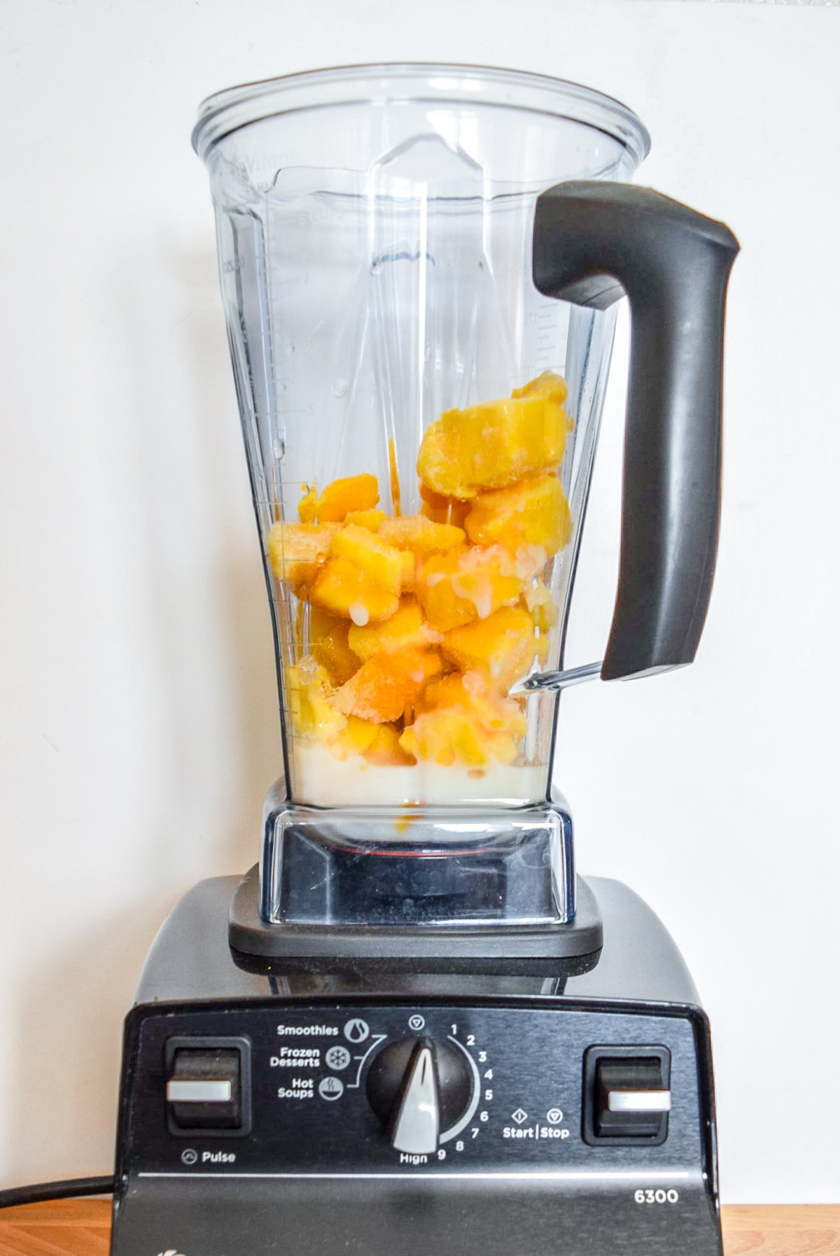 Ingredients for Two-Ingredient Almond Mango Ice Cream in the Vitamix blender from front