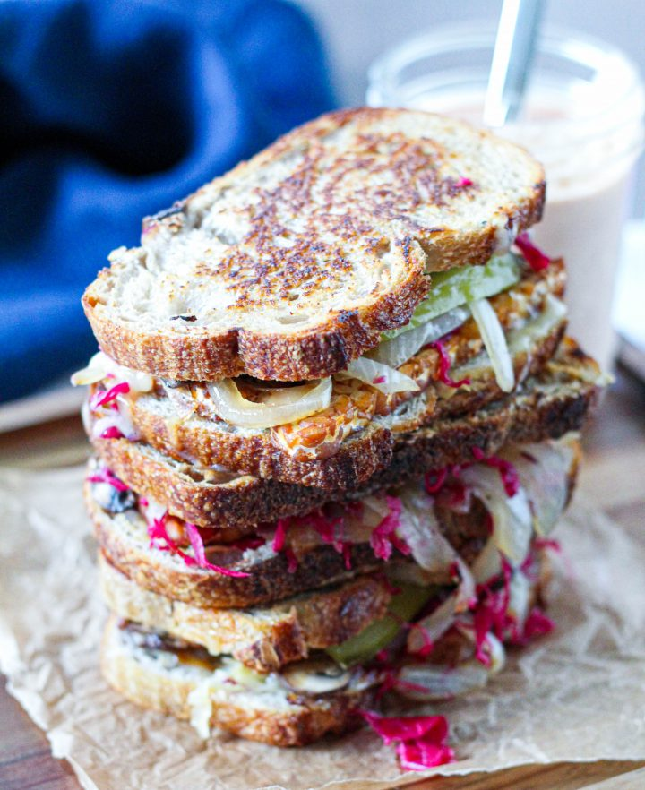 a straight on shot of a stack of 3 tempeh Reubens on a wooden serving board