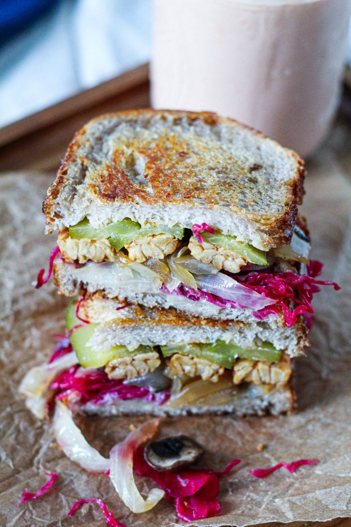 one of the sandwiches sliced in half to show the tempeh bacon, sauerkraut, caramelized onion and mushrooms, pickles, and cheese, on a wooden board