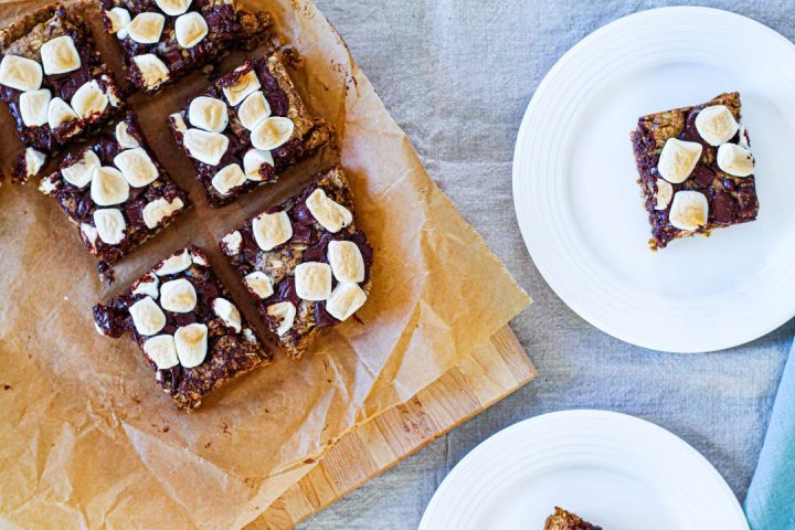 overhead shot of some s'mores bars on parchment paper and two s'mores bars on white plates