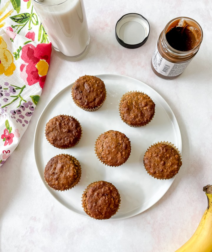 overhead shot of a plate of the muffins with a glass of almond milk