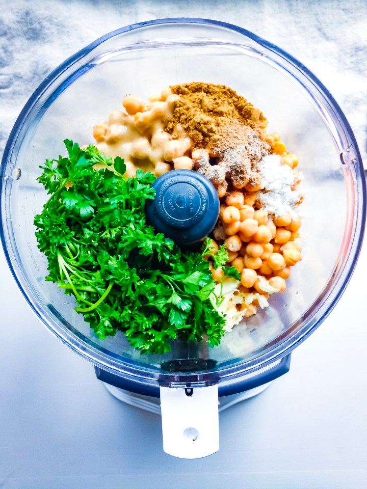 A head-on shot displaying falafel ingredients in a food processor.