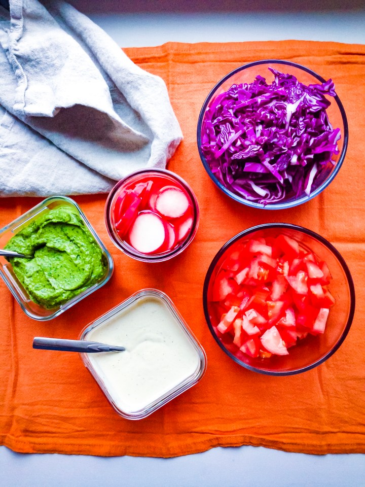 Falafel taco accompaniments: avocado zhoug sauce, yogurt tahini sauce, tomato, cabbage, and pickled radishes