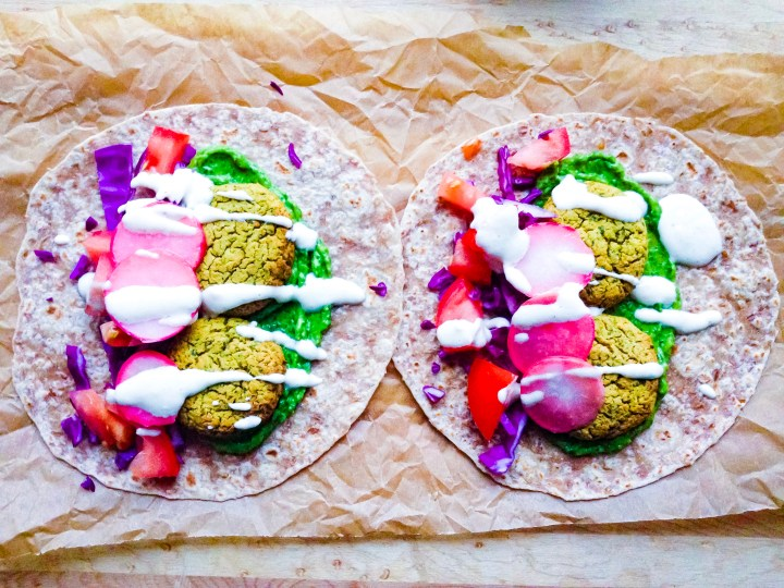 A head-on shot displaying falafel tacos with zhoug, tahini sauce, and vegetables.