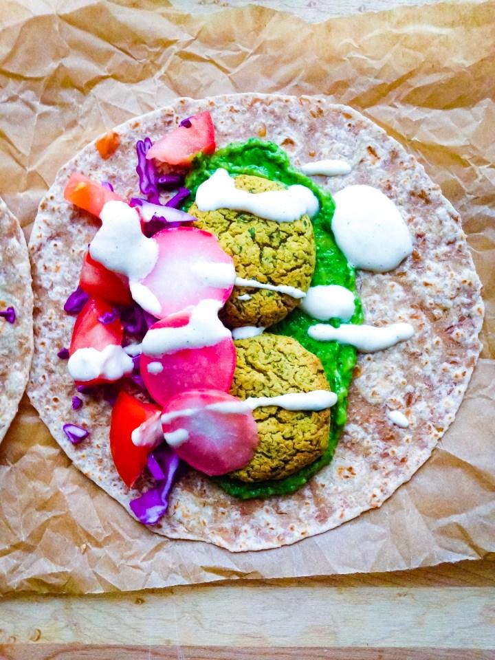 A falafel taco with avocado zhoug, yogurt tahini sauce, and pickled radishes.