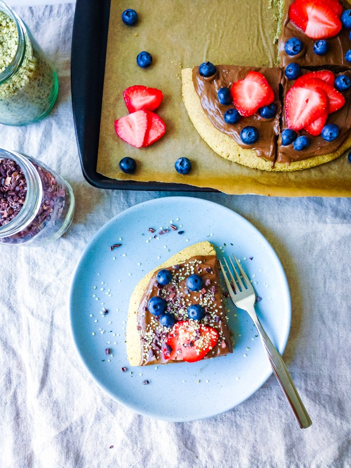 A slice of healthy vegan dessert pizza with fudge icing, blueberries, strawberries, hemp hearts, and cacao nibs