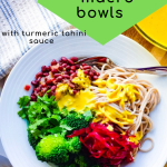 an overhead view of the vegan macro bowl with a portion of soba noodles, steamed broccoli, sauerkraut, cilantro, adzuki beans, and turmeric tahini sauce.