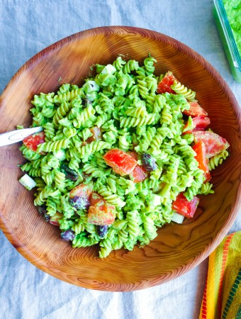 A Green Goddess Pesto Pasta Salad made with avocado, cashews, and basil, tossed with chickpea pasta noodles and olives
