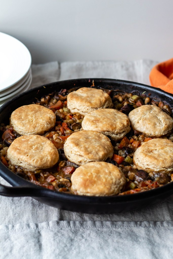 the finished product: the cast iron skillet has just been taken out of the oven and the white bean/mushroom stew is covered in golden buttery vegan spelt biscuits.
