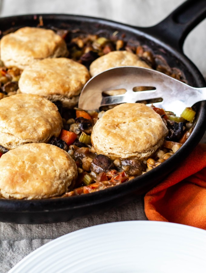A vegan pot pie made with white beans, vegetables, herbs, and spelt flour biscuits. A close up of the pie in a cast iron skillet.