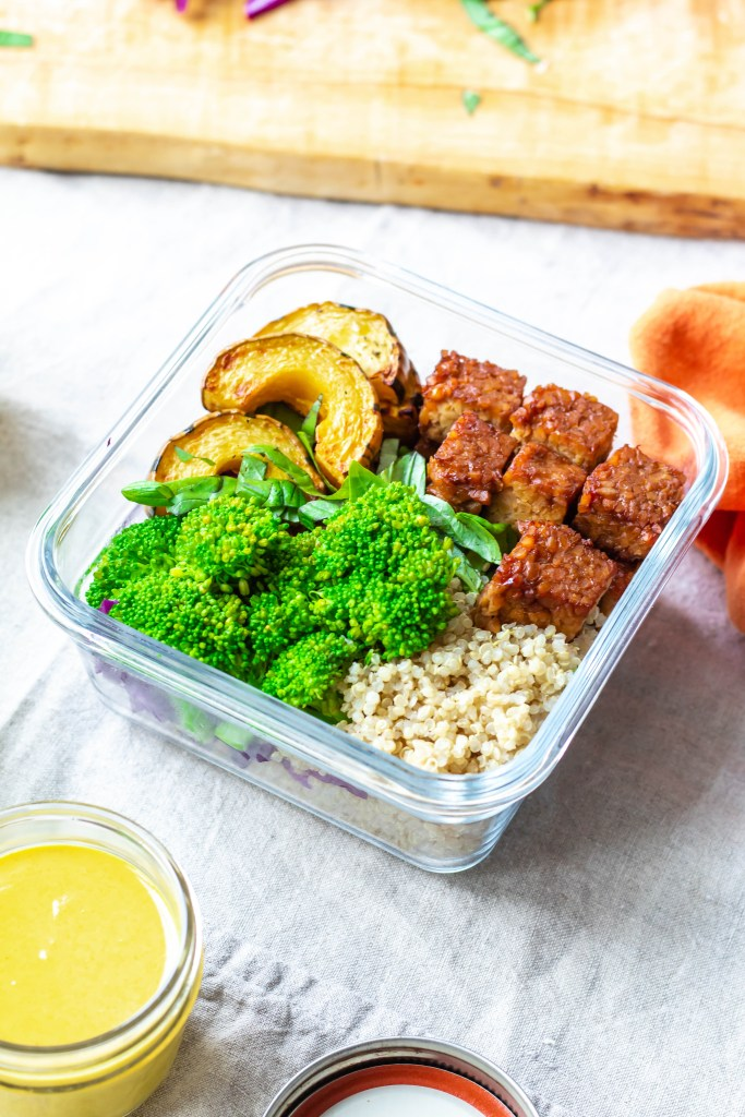 These vegan meal prep tempeh buddha bowls contain roasted delicata squash, maple balsamic tempeh, steamed broccoli, shredded cabbage, herbs, quinoa, and turmeric tahini sauce.