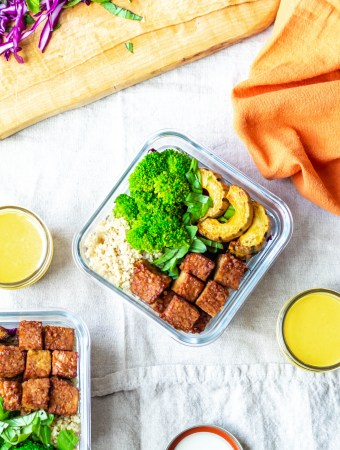 Vegan Lunch Prep Tempeh and Roasted Squash Buddha Bowls Recipe (an overhead photo of all of the components in a container with turmeric tahini sauce on the side)