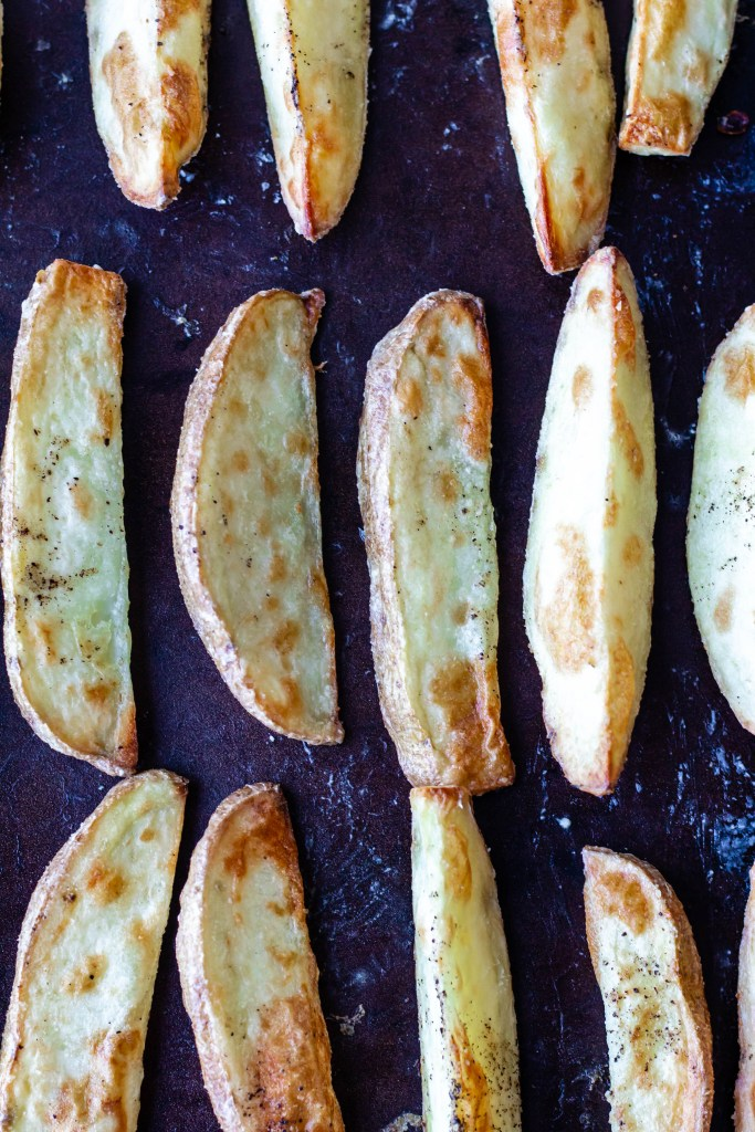 the baked oven fries are shown on a baking sheet after being roasted for 30 minutes. They look browned and crispy.