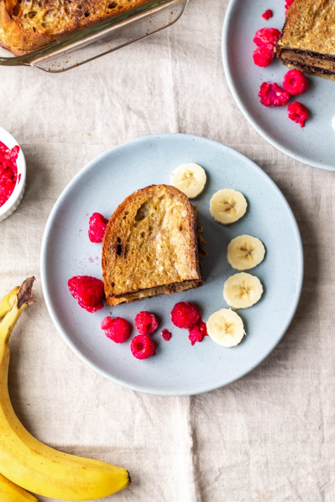 Dairy Free Nutella French Toast Bake (overhead shot of a sandwich with raspberries, banana)