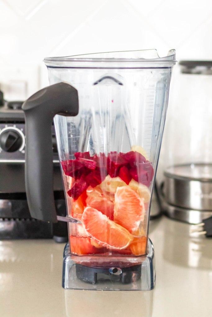 energizing beet grapefruit juice ingredients in the blender ready to go: beet, grapefruit, lemon, orange, cayenne